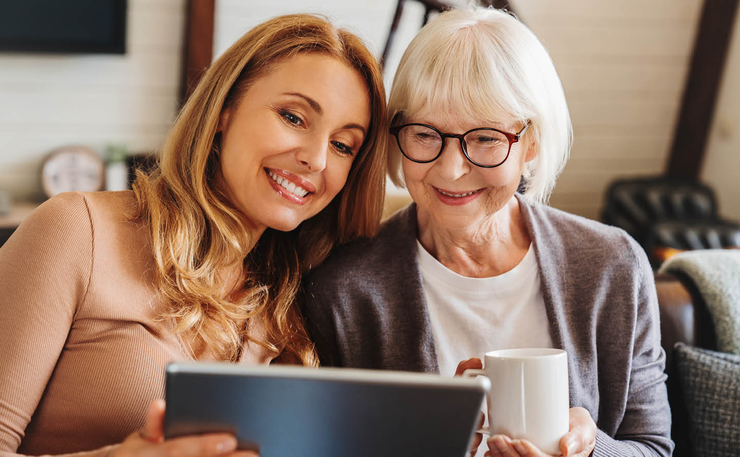 Daughter with senior mother looking at a tablet and smiling