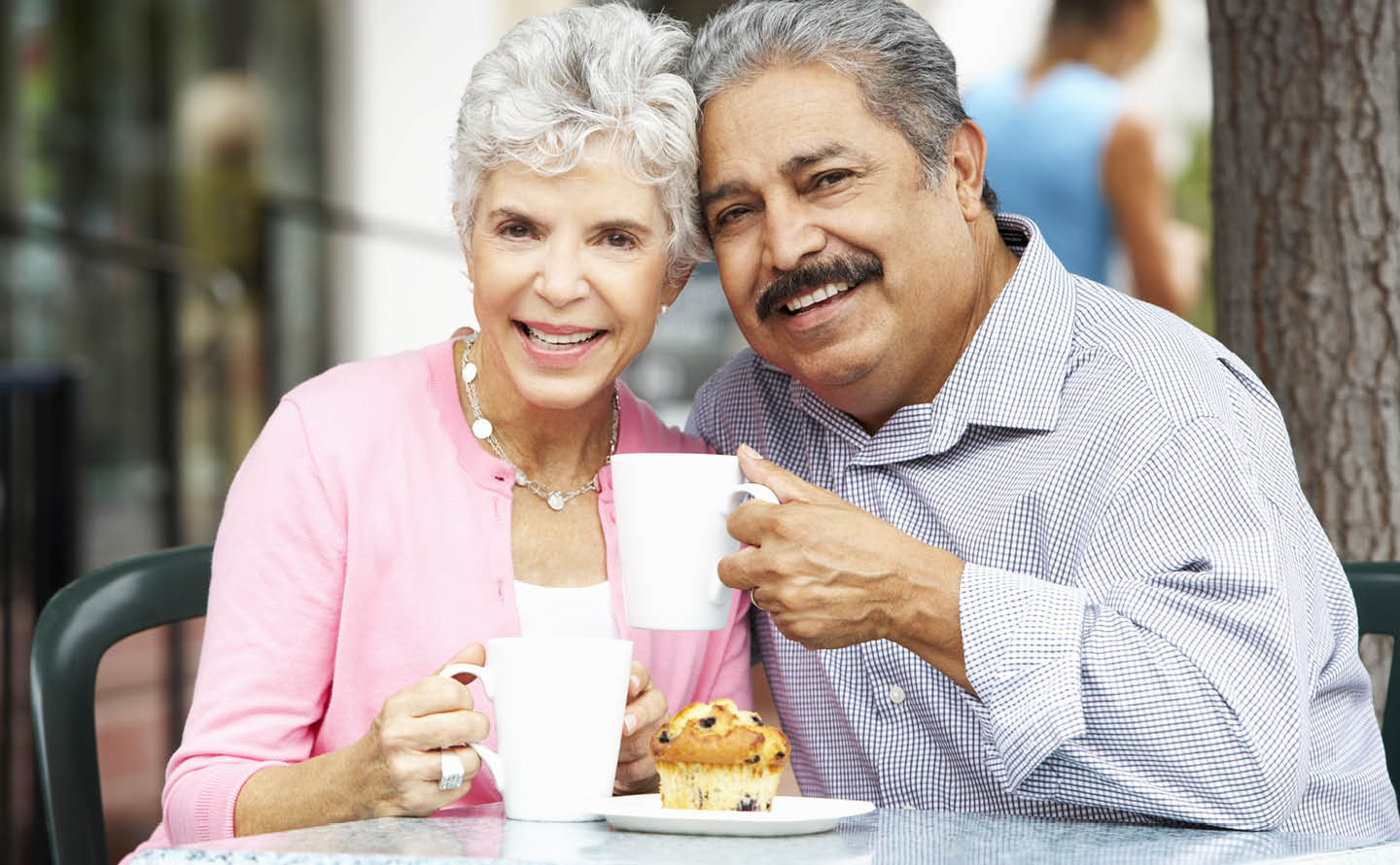 Senior couple enjoying coffee and muffins outdoors.