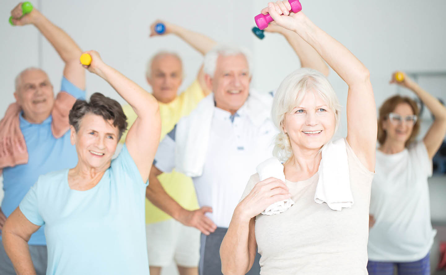Seniors in a group exercise class with weights in hand