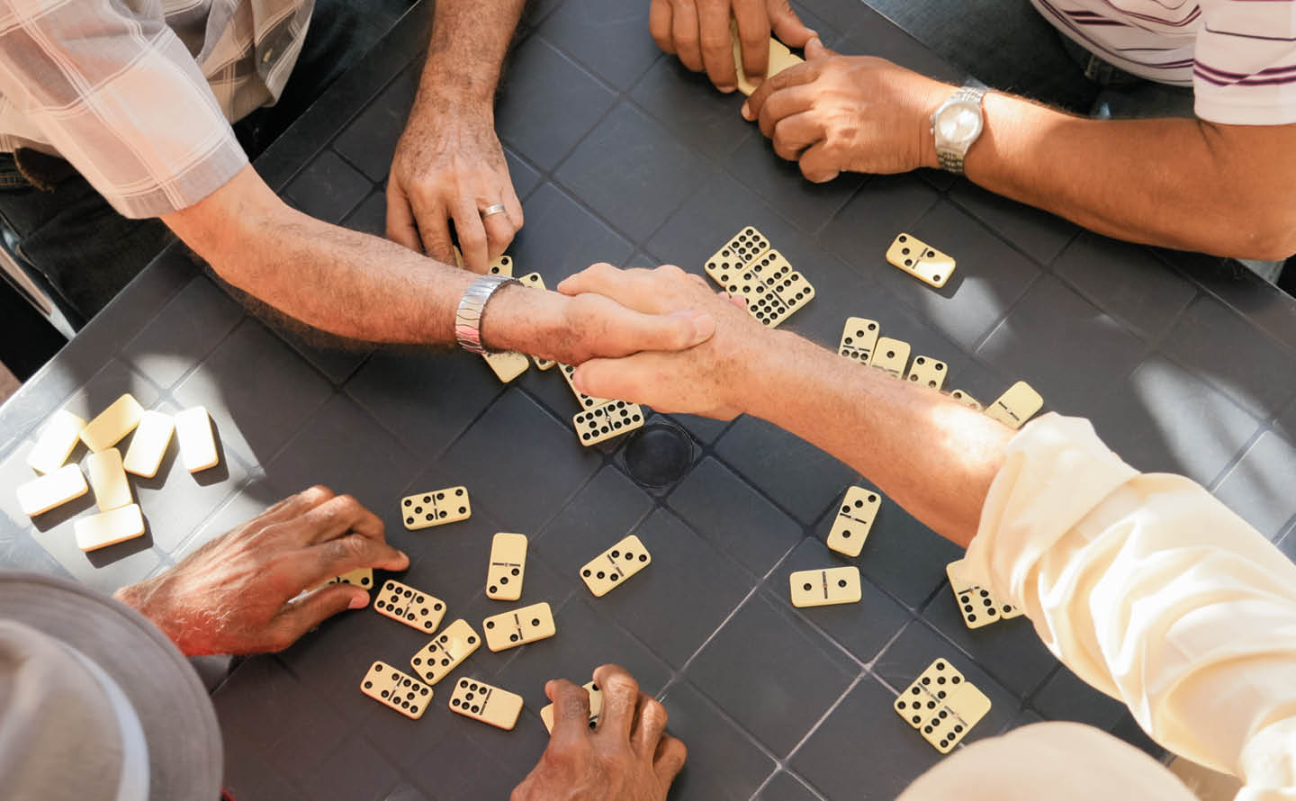 A group of four people playing dominos; two of the players are shaking hands.