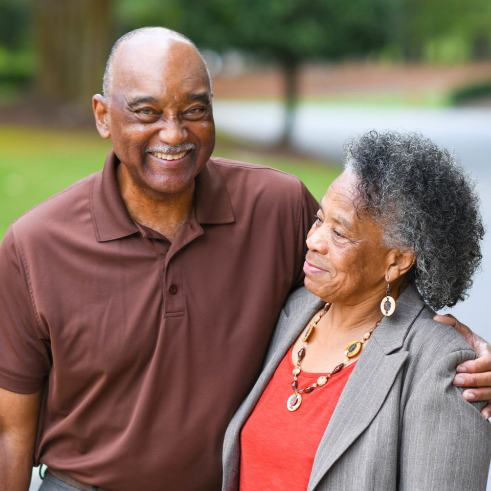 Senior couple with arms around each other smiling