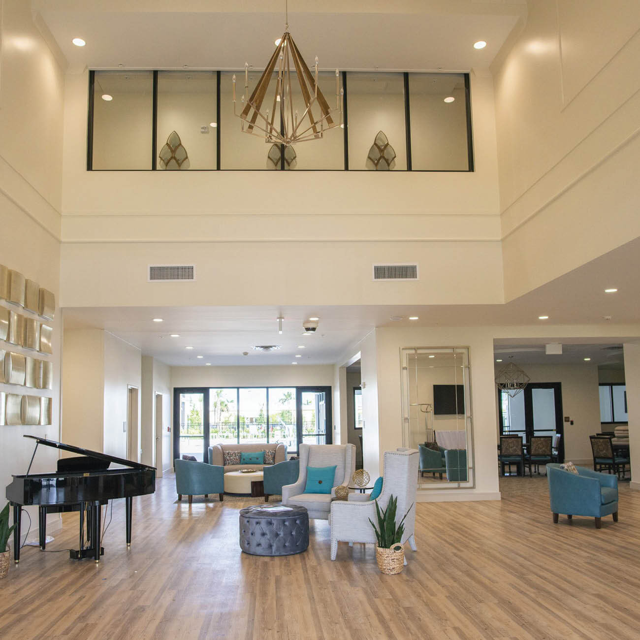Lobby at Highpoint at Cape Coral includes piano, multiple seating areas and large windows.