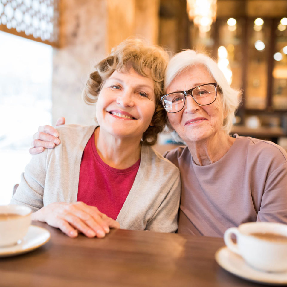 Senior mother and daughter with arms around each other, smiling at a coffee shop