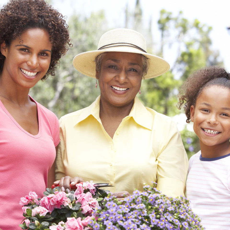 Grandmother, daughter and grand daughter holding flowers