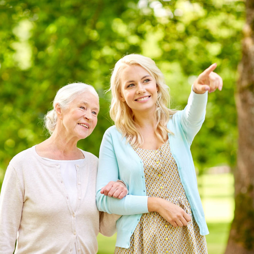 Senior woman walking arm in arm with her daughter outside.