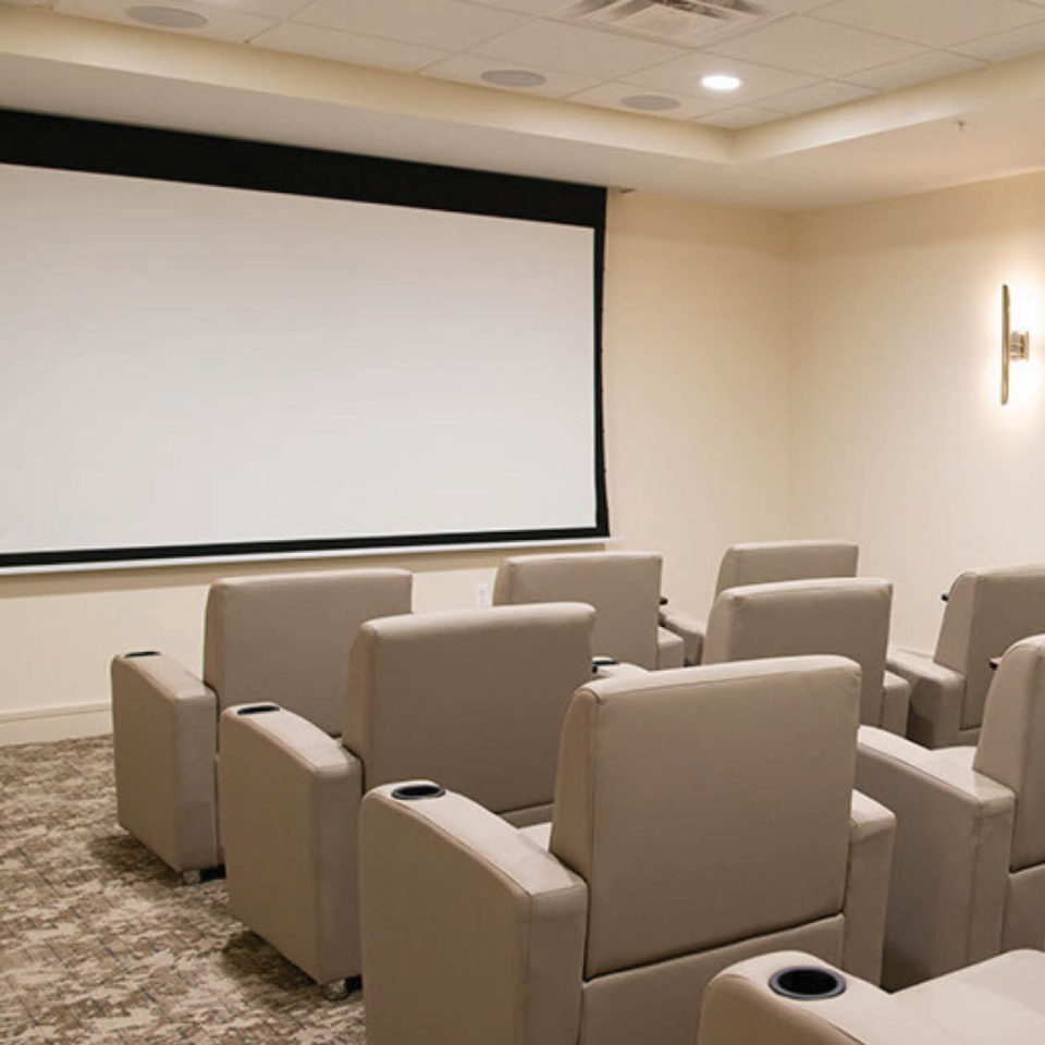 Theatre room at Highpoint at Cape Coral. Includes many reclining leather movie theatre seats and a large projector screen.