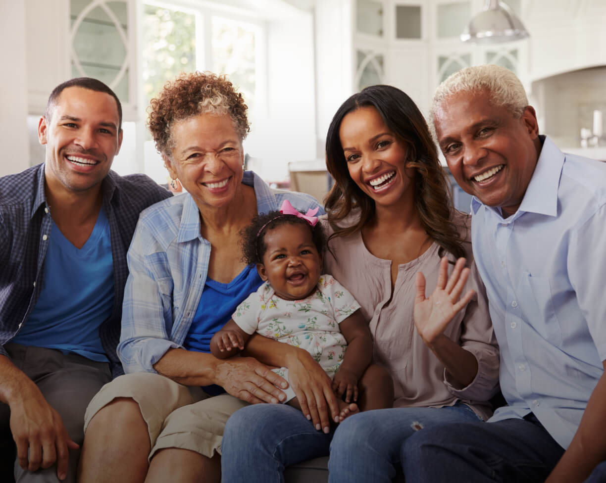 Multi generational family, grandparents, parents and child, smiling and waving.