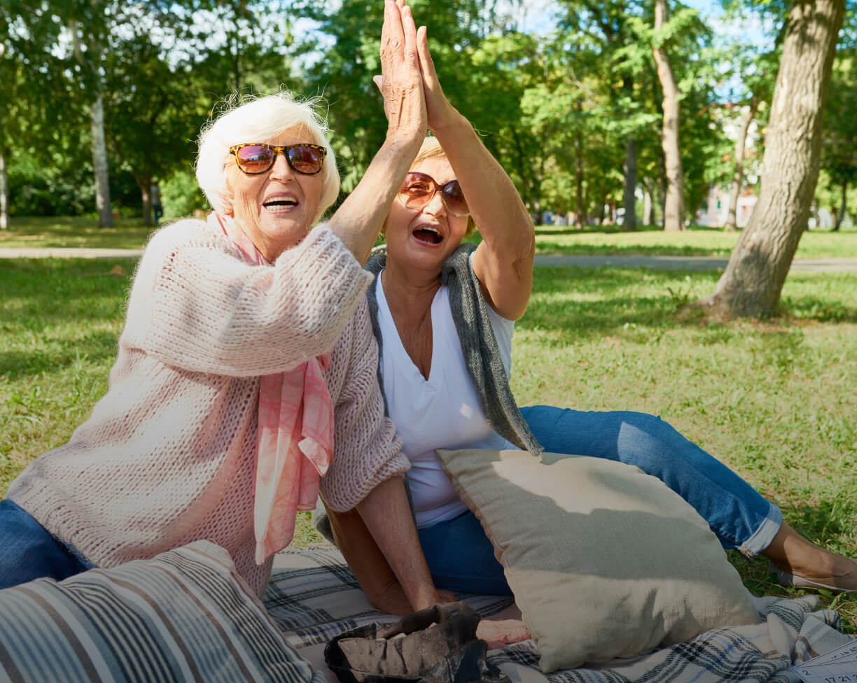 Two female friends on picnic blanket giving each other a high five.