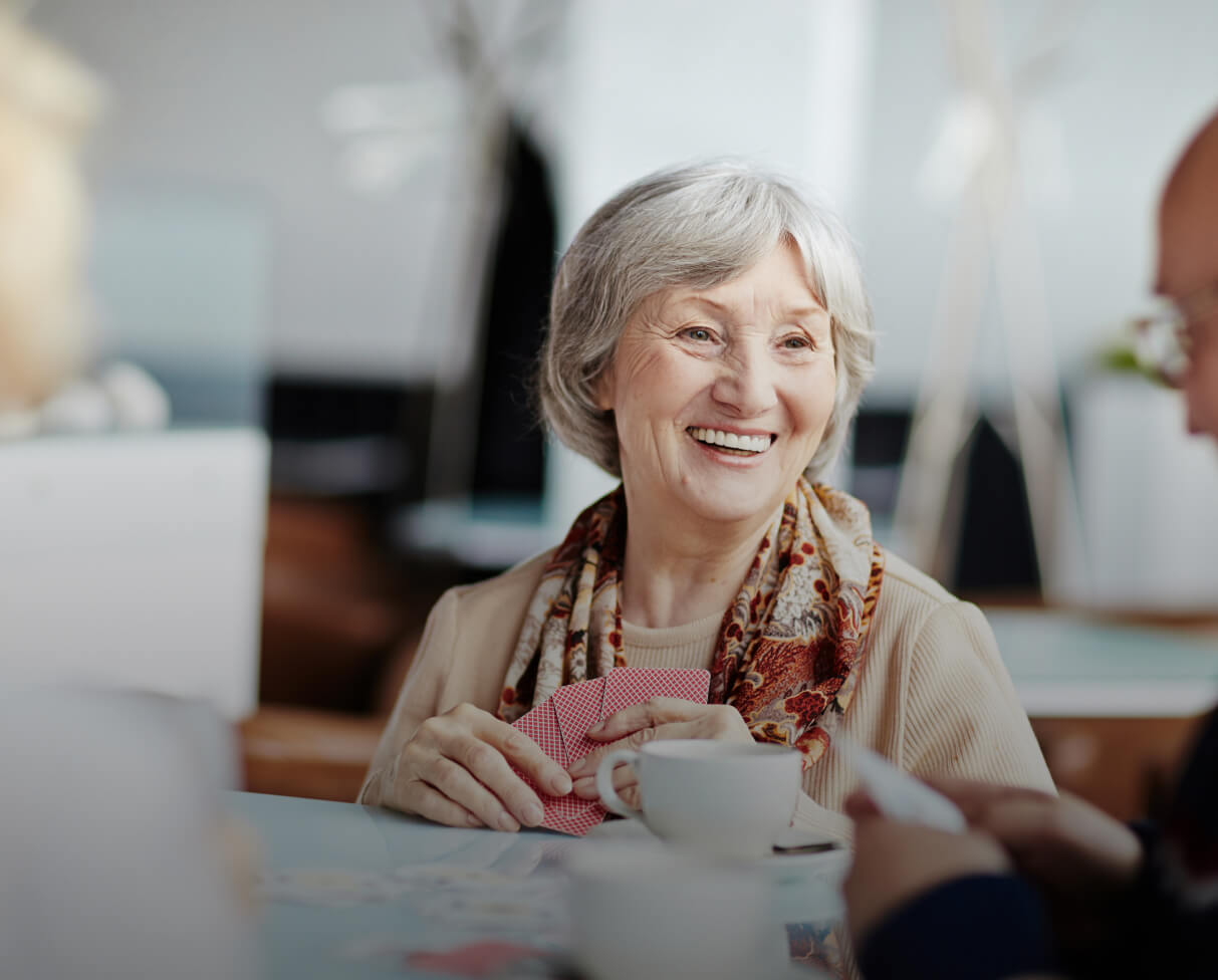 Woman with grey hair playing a card game with another person who is out of focus