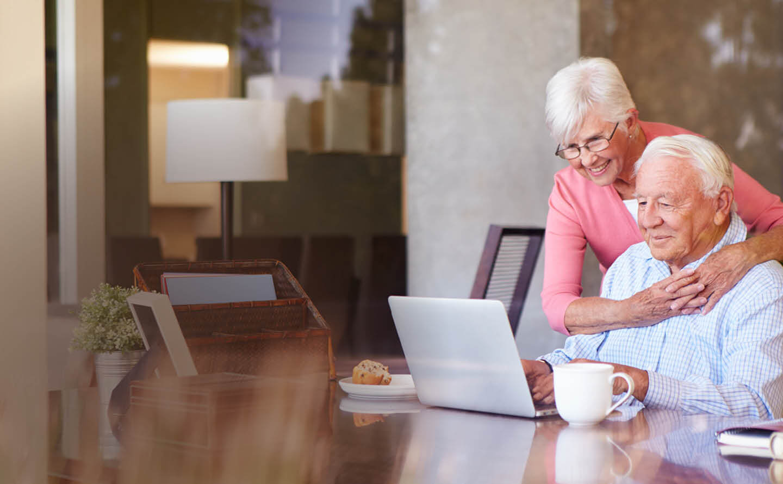 Senior couple enjoying breakfast while educating themselves online