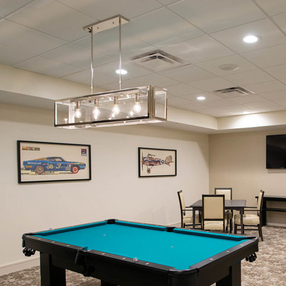 Game room at Highpoint at Cape Coral including pool table and card table.
