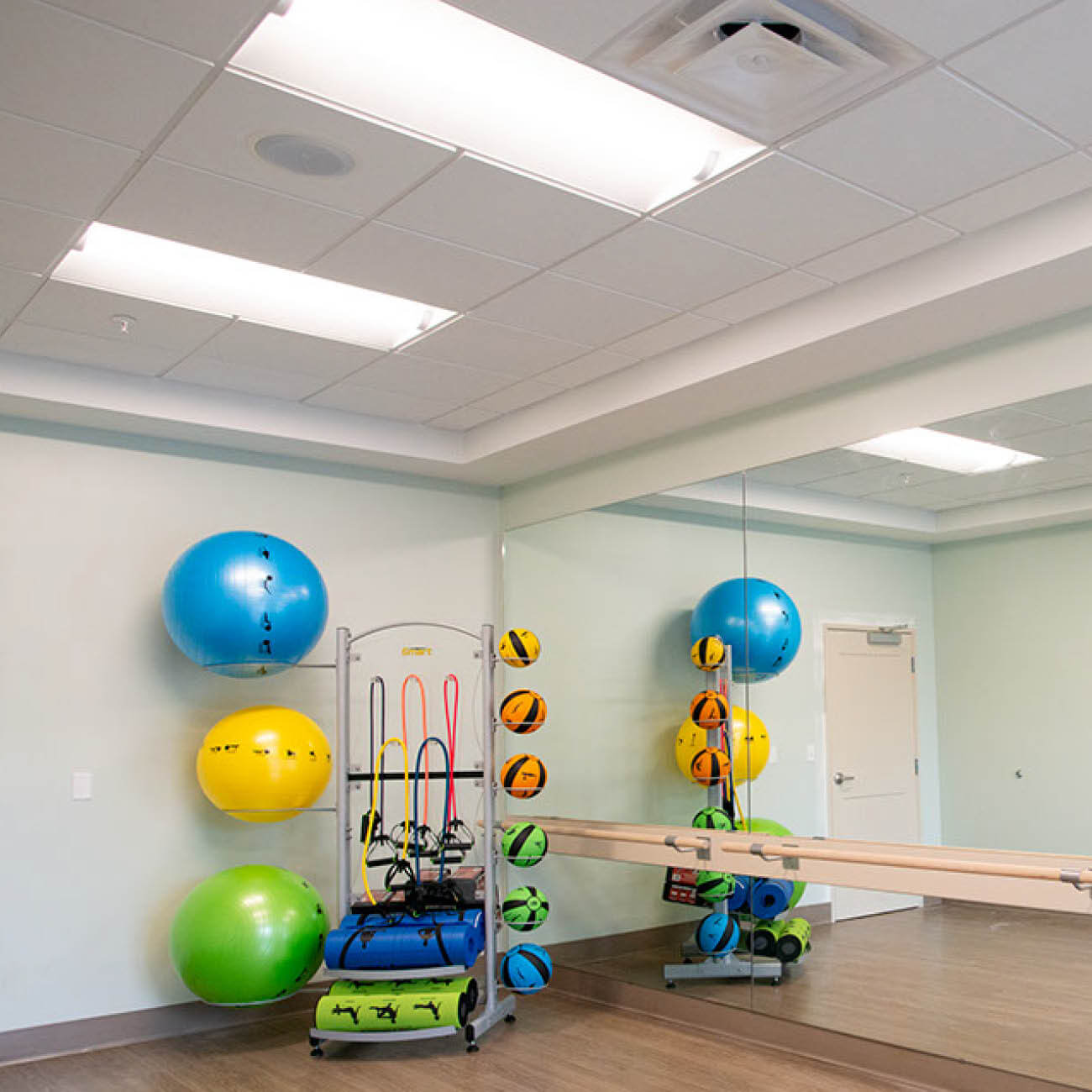 Fitness room at Highpoint at Cape Coral including large mirror, ballet bar, various weighted balls and other exercise accessories.