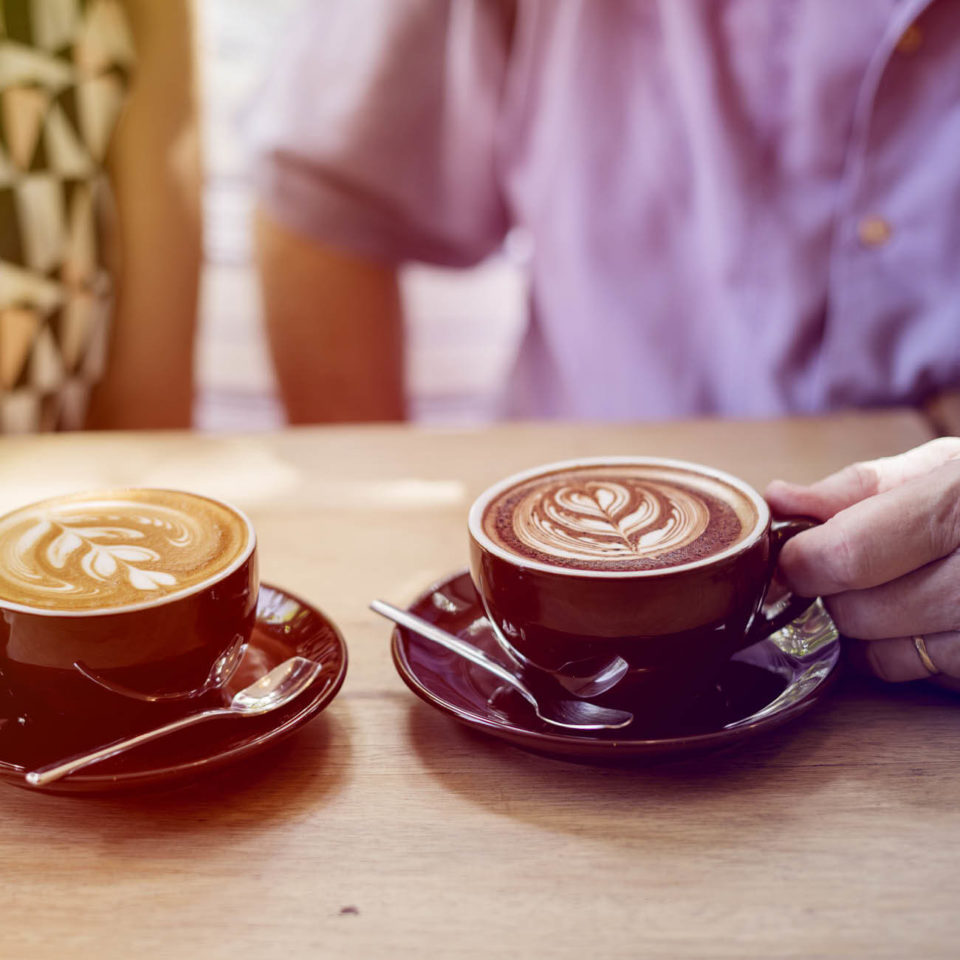 Two people out of focus enjoying lattes together.